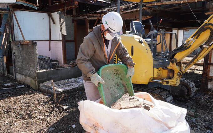 解体ゴミをズタ袋に入れている作業員の方